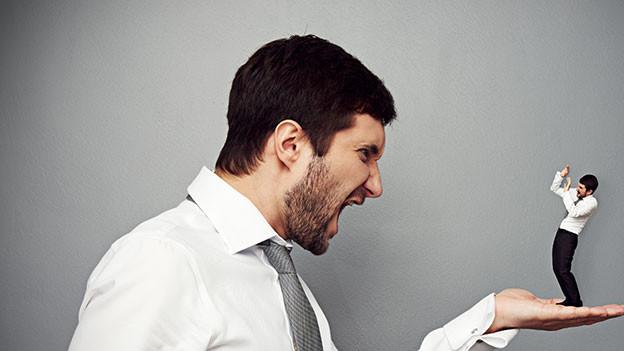Mann hält sein Miniatur-Konterfei in der Hand und schreit es an.