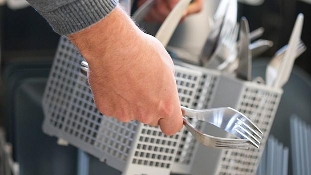 Geschirr wird in den Geschirrspüler gelegt.