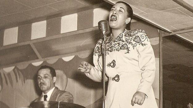 Billie Holiday während Konzert mit Band.