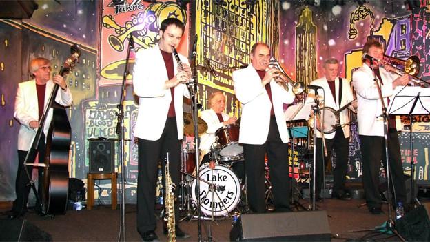 Sechs Musiker mit dunkelroten Shirts und weissen Westen bei einem Auftritt vor einer bunten Bühnenkulisse.