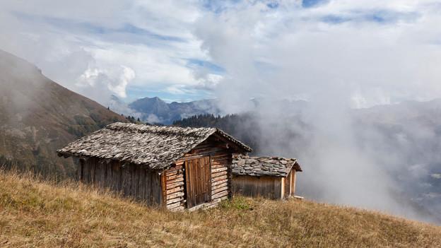 Nebel zieht aus dem Tal über die Holzhütten auf der Alp.