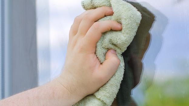 Männliche Hand reinigt Fenster.