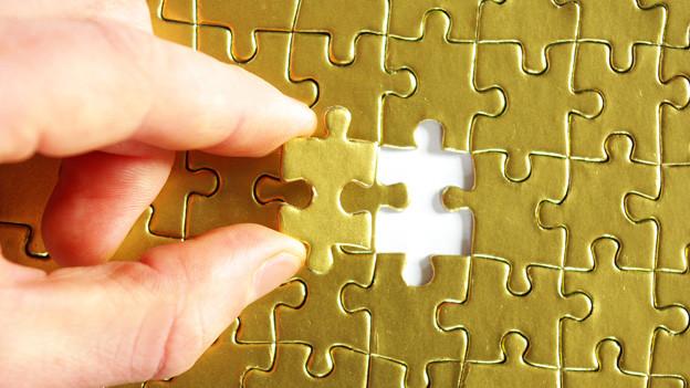 Eine Hand platziert den letzten Teil in der Mitte eines Puzzles.