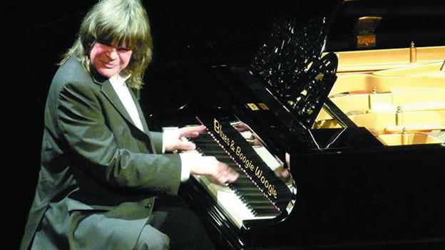 Der Pianist sitzt spielend am Piano und blickt dabei schmunzelnd Richtung Publikum.