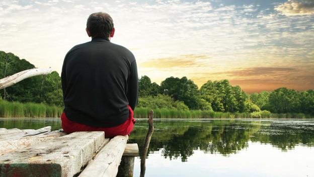 Ein Mann sitzt entspannt auf einem Bootssteg am Rande eines Sees.