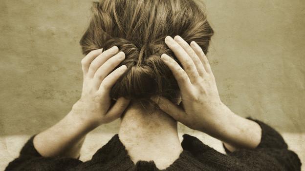 Ein auf alt gemachtes Bild mit einer Frau, die ihre Haare zu einem Dutt zusammengebunden hat.