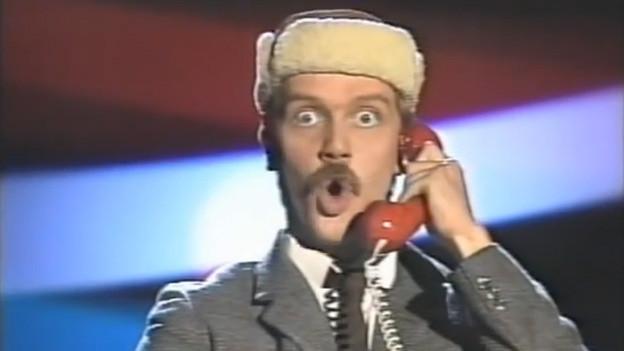 Ein Mann mit einer Pelzmütze telefoniert über ein rotes Telefon.