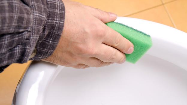 Ein Mann reinigt mit einem Schwamm die Toilettenschüssel.