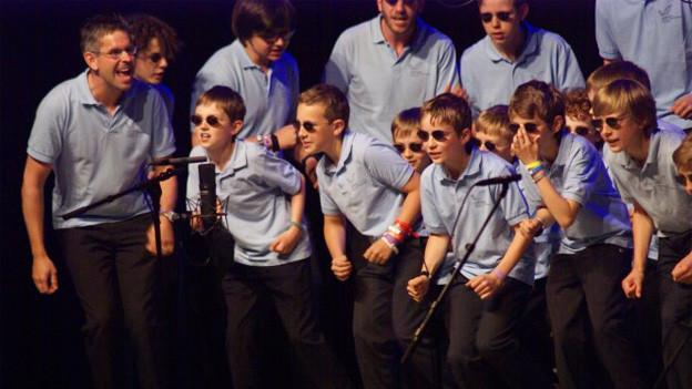 Junge Sänger in blauen Hemden und mit Sonnenbrille in übermütiger Pose während eines Auftritts.