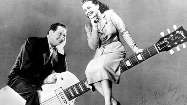 Les Paul und Mary Ford sitzen auf einer überdimensional-grossen Gitarre.