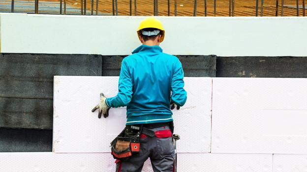 Ein Bauarbeiter montiert Isolierplatten an einer Hausfassade.