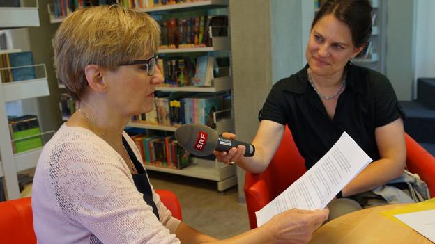 Heidi Büchel sitzt in der Bibliothek und liest am Mikrofon eine Geschichte vor.