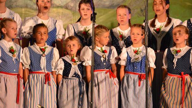 Mädchen und junge Frauen in Trachten singen im Chor.