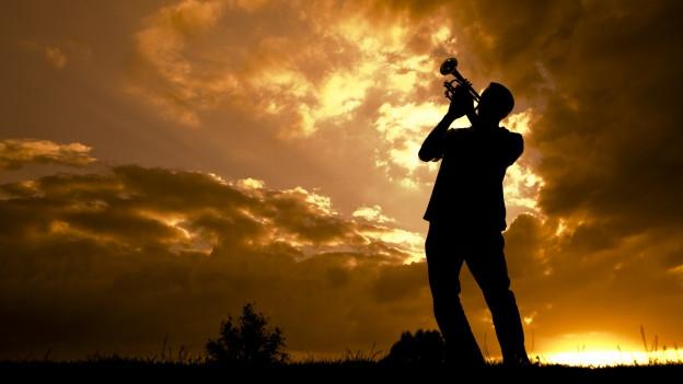 Jazztrompeter vor dramatischem Hintergrund.