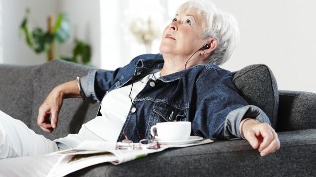 Frau sitzt auf bequemem Sofa mit Kaffeetasse und Kopfhörer.