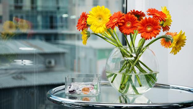 Blumen in einer Vase aus Glas auf einem Glastisch.
