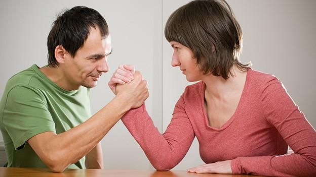 Ein Mann und eine Frau messen sich beim Armdrücken.