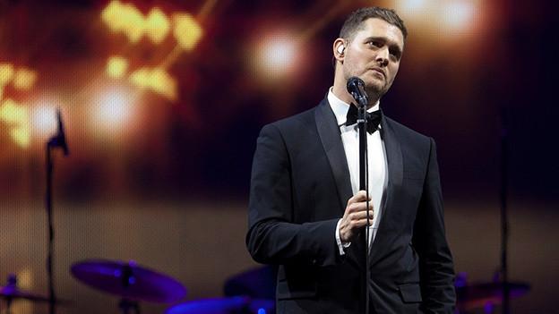 Der Sänger steht bei einem Auftritt im Scheinwerferlicht nachdenklich vor dem Mikrofon.