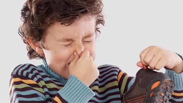 Ein Bub hält einen Turnschuh hoch und hält sich dabei die Nase zu.