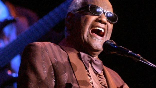Ray Charles auf Bühne an Piano.