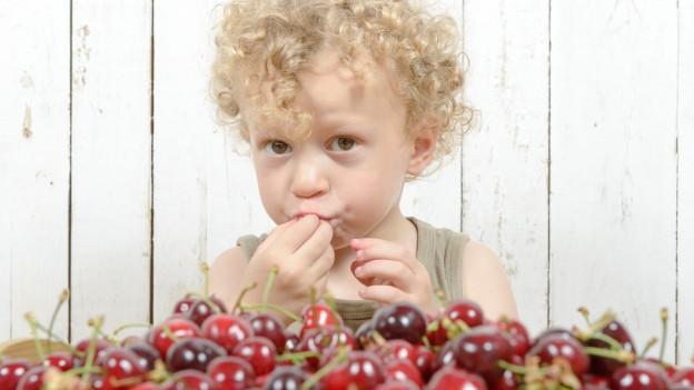 Kleiner Junge isst Kirschen.