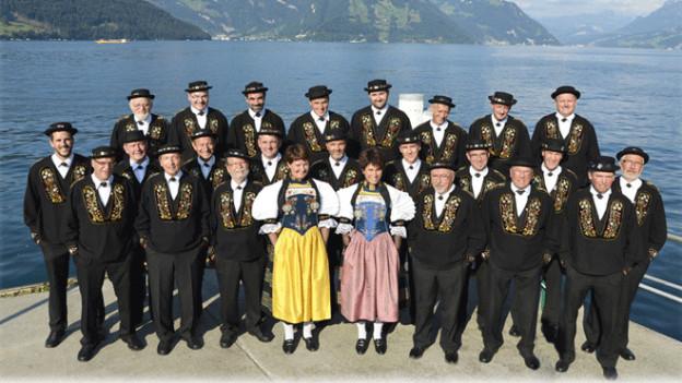 Die Jodlerinnen und Jodler stehen auf einem Steg am Ufer eines Sees.