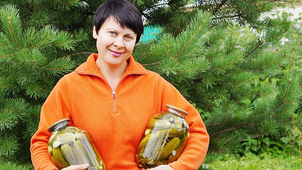Eine Frau mit kurzen dunklen Haaren hält zwei grosse Gläser mit Essiggurken in den Armen.