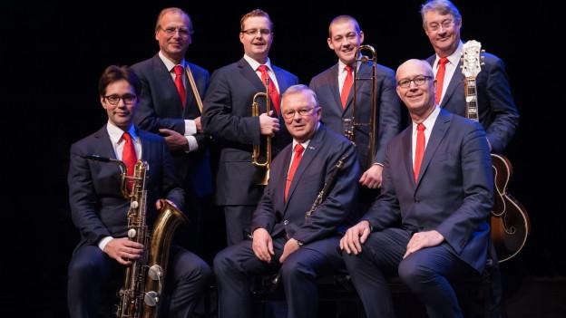 Band im Anzug mit roten Krawatten und Instrumenten.