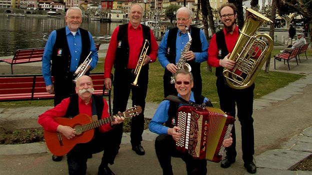 Sechs Musikanten mit roten oder blauen Hemden unter einem schwarzen Gilet posieren mit ihren Instrumenten in einem Park am See.