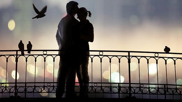 Ein verliebtes Paar steht in der Abenddämmerung auf einer Brücke.