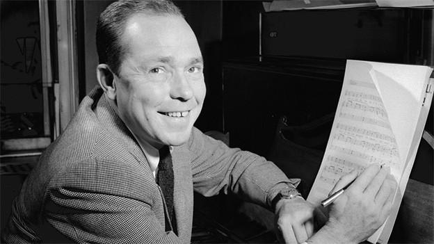 Schwarz-Weiss-Fotografie mit dem Komponisten, der mit einem Notenblatt am Klavier sitzt.
