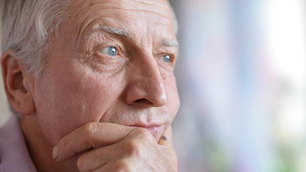 Ein älterer Mann stützt sein Gesicht gedankenversunken in seine Hand.
