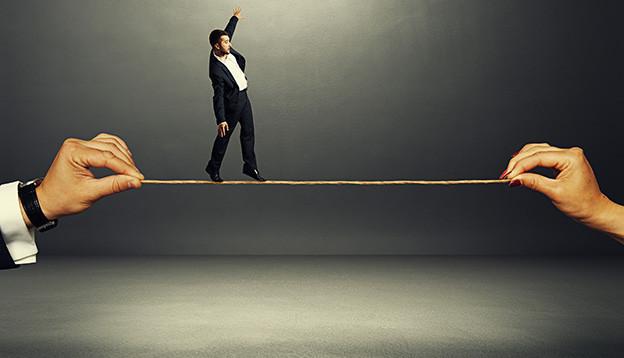 Bildcollage mit einem Mann, der auf einem Seil balanciert, das von zwei grossen Händen gehalten wird.