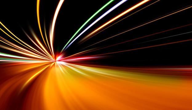 Szene bei Nacht, wobei die Lichter schnell fahrender Fahrzeuge Strahlen erzeugen.
