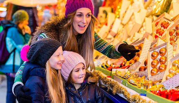Eine junge Mutter und ihre zwei kleinen Mädchen bestaunen die Weihnachtsdekoration.