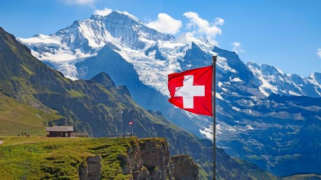 Schweizer Flagge weht auf Berg.