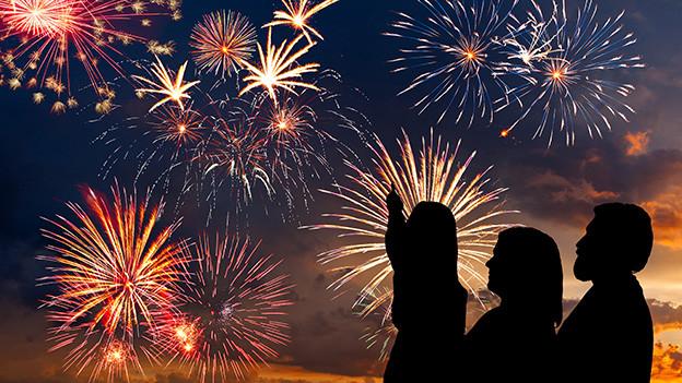 Silhouette einer dreiköpfigen Familie, die ein Feuerwerk bestaunt.