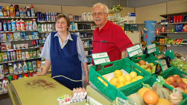 Eine Frau und ein Mann in einem Laden voller Regale, die mit Lebensmitteln und anderen Artikeln gefüllt sind.