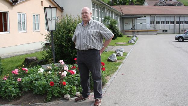 Josef Müller steht vor dem Eingang eines Industriegebäudes.