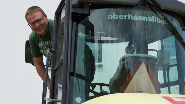 Sämi Studer blickt fröhlich aus der Führerkabine eines Bagger.