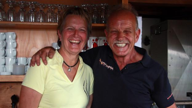 Das Ehepaar steht hinter einer Theke und lacht übermütig in die Kamera.