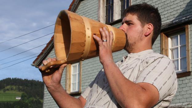 Ein Mann hält ein trichterartiges Gefäss aus Holz vor dem Mund und singt.
