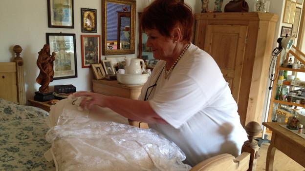 Luzia Brand steht vor einem grossen Bett und bereitet für den neuen Erdenbürger ein weisses Spitzentuch über einem weissen Kissen aus.