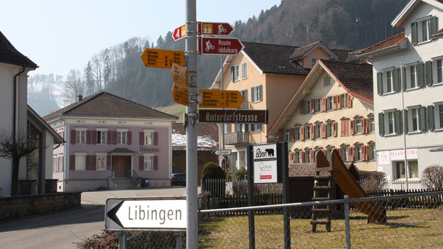 Strassenkreuzung mit Wegweisern vor Häusern im typischen Toggenburger Baustil.