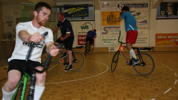 Drei Männer auf speziellen Fahrrädern, die über eine hohe wendige Lenkstange verfügen.