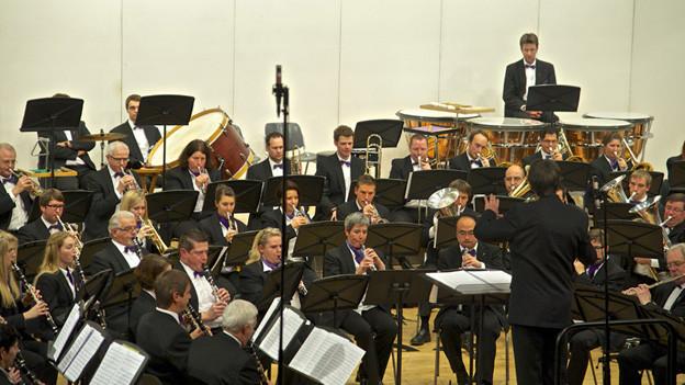 Die Musikantinnen und Musikanten sitzen im Halbkreis auf einer Bühne.
