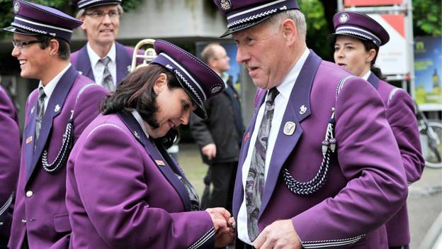 Frauen und Männer in lila Uniformen lachend auf einer verkehrsfreien Strasse.