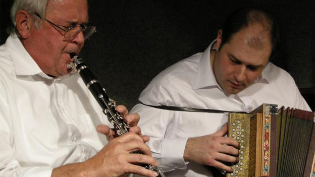 Ein älterer Mann spielt Klarinette, ein jüngerer Schwyzerörgeli.