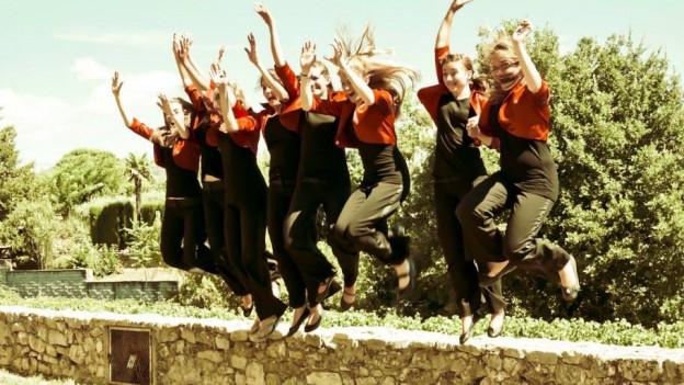Sieben junge Frauen bilden den Chor. Sie springen gleichzeitig über eine Steinmauer.