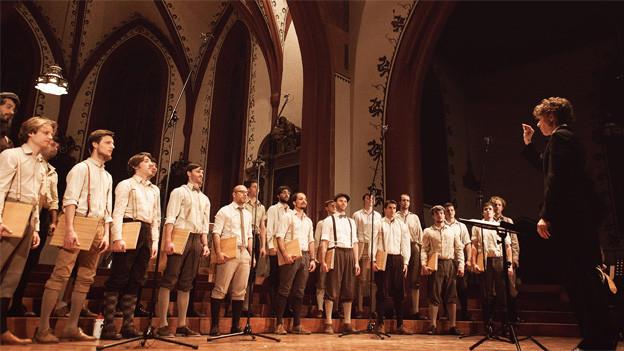 Die Sänger stehen nebeneinander in einer Reihe und tragen alle Kleider aus alten Zeiten.